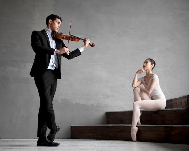 Balerina słucha muzyka grającego na skrzypcach