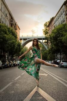 Balerina tańczy na ulicy w zielonej sukience