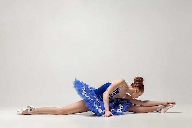 Balerina ubrana w niebieską sukienkę i buty pointe siedząca na sznurku na białym tle