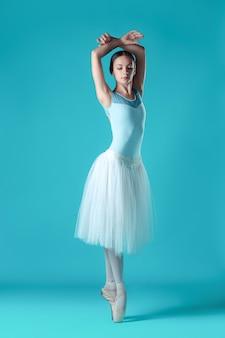 Balerina w białej sukni pozuje na palcach, przestrzeń pracowni.