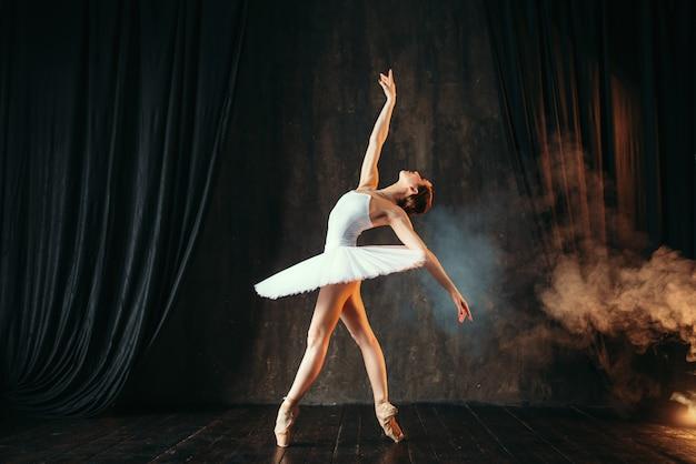 Balerina w białej sukni tańczy w klasie baletu