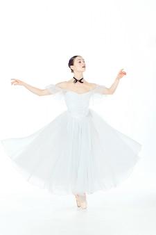 Balerina w biel sukni pozuje na pointe butach, pracowniany tło.