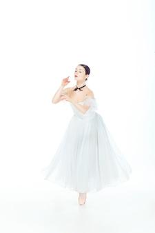 Balerina w biel sukni pozuje na pointe butach, studio.