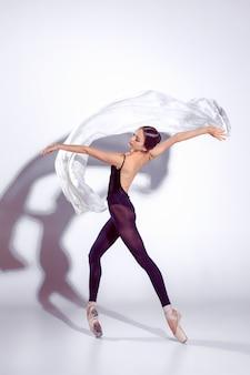 Balerina w czarnym stroju pozuje na palcach.