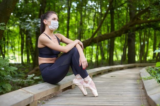 Balerina w masce i pointe ćwiczy na drewnianej ścieżce w leśnym parku. koncepcja bezpiecznego treningu na świeżym powietrzu