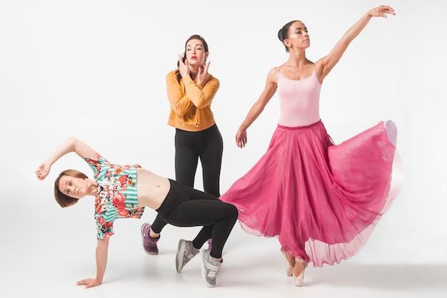 Balerina z dwa żeńskimi tancerzami przeciw białemu tłu