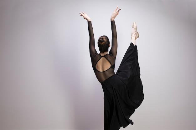 Balerina z tyłu z jedną nogą do góry