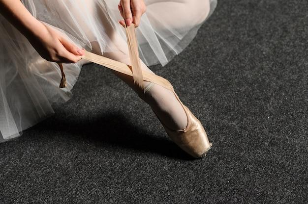 Balerina zawiązuje wstążkę swojego pointe buta