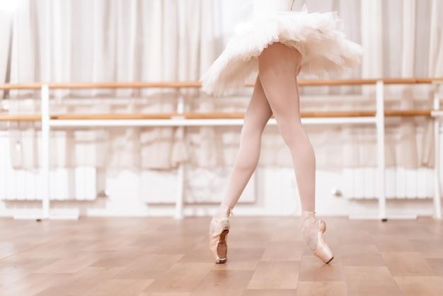 Baleriny nogi stoi na podłodze w studio tańca.