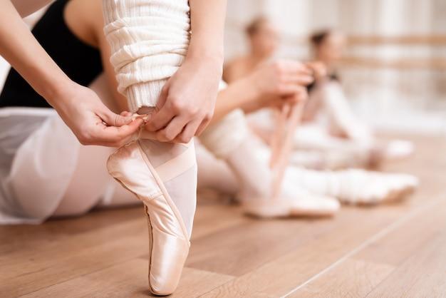 Baleriny poprawiają buty pointe w sali tanecznej.