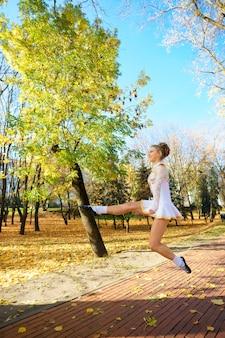 Baleriny tańczą w parku przyrody wśród jesiennych liści.