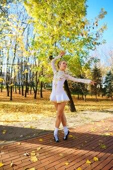 Baleriny tańczące na łonie natury wśród jesiennych liści na pointach.