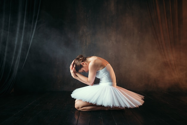 Baleriny w białej sukni siedzi na scenie teatralnej, widok z boku. klasyczna tancerka baletowa w klasie na czarno
