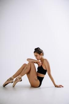 Balet mody. młoda kobieta tancerka baletowa w czarnym body na białym tle studio. kaukaska balerina jak modelka. styl, współczesna koncepcja choreografii. kreatywne zdjęcie artystyczne.