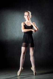 Balet. wizerunek elastycznej ślicznej baleriny taniec w studiu. piękna młoda tancerka. mała czarna sukienka.