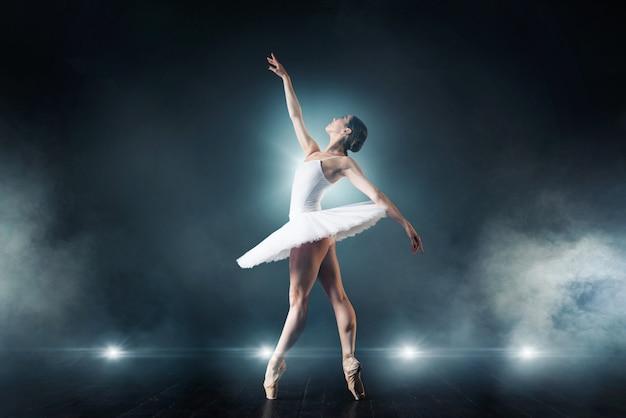 Baletnica w białej sukni tańczy na scenie w teatrze. pełen wdzięku trening baleriny w klasie