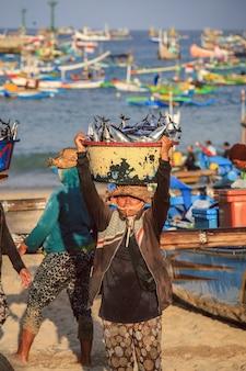 Bali, indonezja - 6 lipca 2017: balijski sprzedawca ryb niesie ryby w basenie w porannym targu na plaży jimbaran