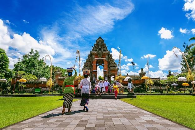 Balijczycy w tradycyjnych strojach podczas ceremonii religijnej w świątyni pura taman ayun na bali w indonezji