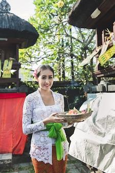 Balijczyk w tradycyjnych strojach przynoszących canang sari