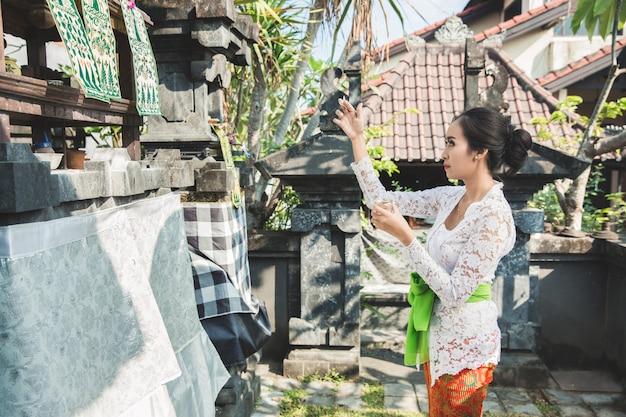 Balijska kobieta robi rytualne ofiarowanie canang sari i modli się