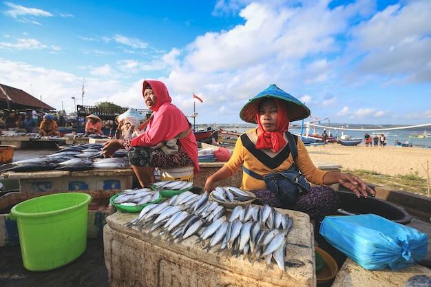 Balijski sprzedawca ryb sprzedaje ryby na porannym targu w kedonganan passer ikan, jimbaran beach