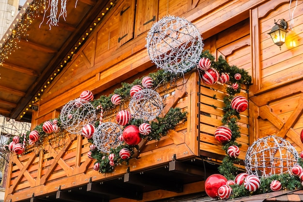 Balkon drewnianego budynku w stylu vintage ozdobiony sztuczną jodłą z girlandą i wieloma czerwonymi i białymi bombkami w zimowy dzień, bez śniegu.