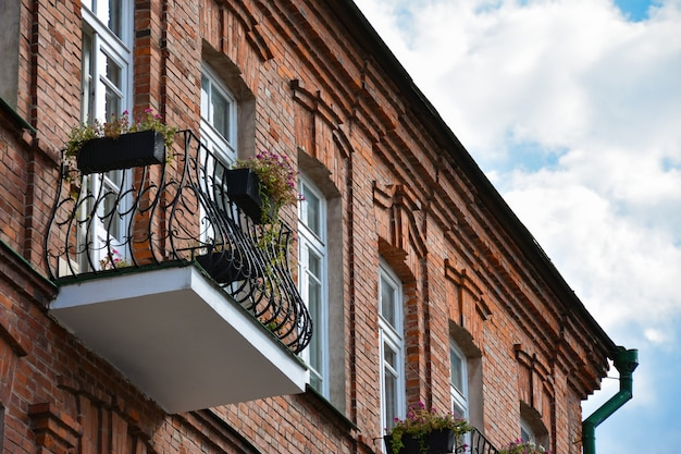 Balkon z kwiatami na starym ceglanym budynku w historycznym centrum miasta