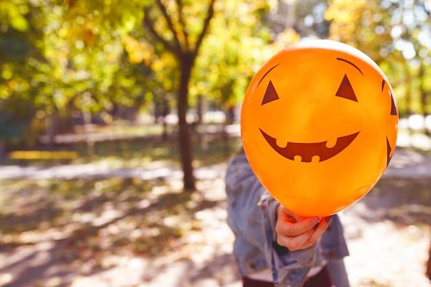 Balon halloween z dyniową twarzą w dłoni
