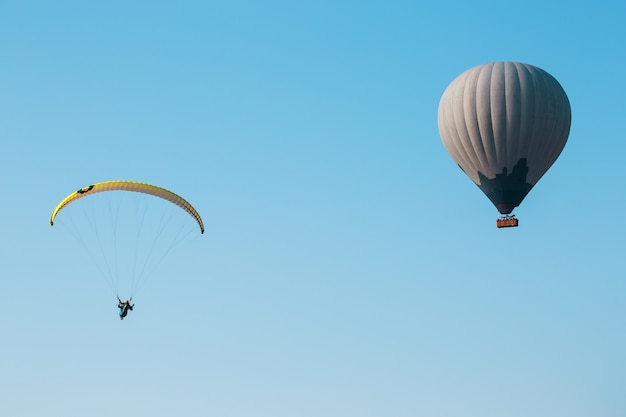 Balon i paralotnia szybują na tle błękitnego nieba.