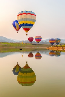 Balon na gorące powietrze nad jeziorem z czasem zachodu słońca