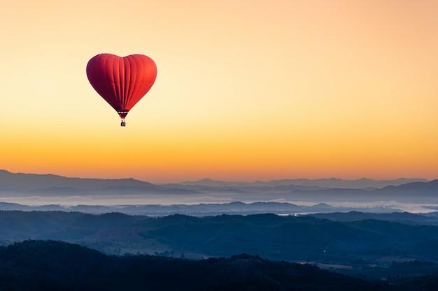 Balon na gorące powietrze w kształcie serca latającego nad górą