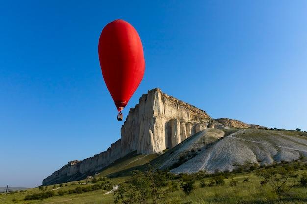 Balon na ogrzane powietrze, czerwony balon w kształcie lecącego serca na tle białej skały. zdjęcie wysokiej jakości