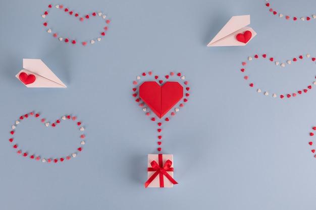 Balon serce papieru origami z pudełko na niebieskim stole