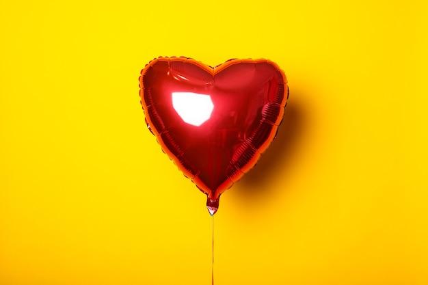 Balon w kształcie serca na żółtym tle.