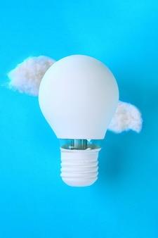 Balon z białej farby malowanej żarówki w chmurach waty.