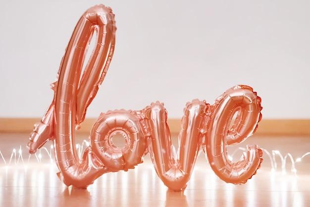 Balon z różowego złota w formie słowa miłość z lekką girlandą.