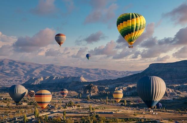 Balony na ogrzane powietrze latają na niebie o zachodzie słońca nad górami.