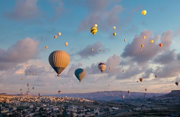 Balony na ogrzane powietrze latają na niebie o zachodzie słońca nad miastem.