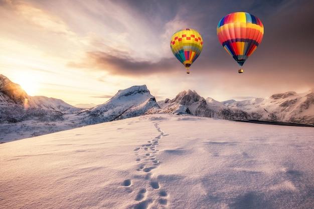 Balony na ogrzane powietrze latające na zaśnieżonej górze ze śladami stóp na szczycie o wschodzie słońca