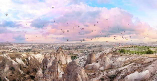 Balony na ogrzane powietrze na różowym porannym niebie nad kapadocją. panorama. goreme, turcja