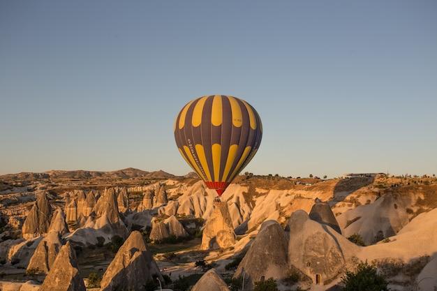 Balony na ogrzane powietrze nad wzgórzami i polami podczas zachodu słońca w kapadocji w turcji