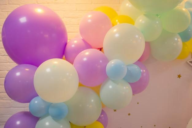 Balony są przymocowane do balustrady werandy. otwarcie sklepu. kremowa ściana, czerwone schody. jasne światło słoneczne i cienie. świąteczny tło ulicy.