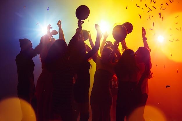 Balony tłum ludzi w sylwetce podnosi ręce na parkiecie na neonowym świetle