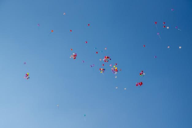 Balony w różnych kolorach latające po błękitnym niebie