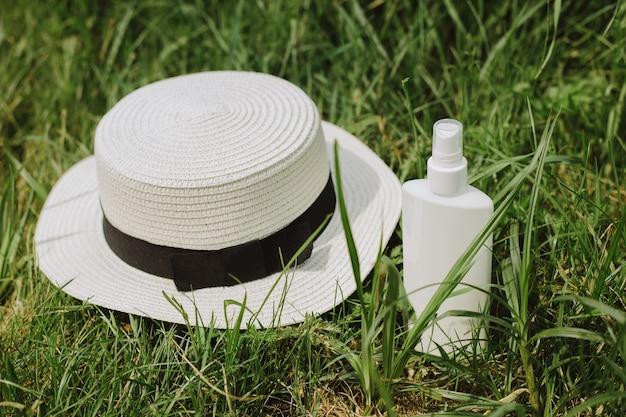 Balsam do opalania i tkany bawełniany kapelusz leżący na zielonej trawie. ochrona przed słońcem