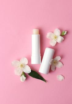 Balsam do ust i kwiaty na kolorowym tle zbliżenie