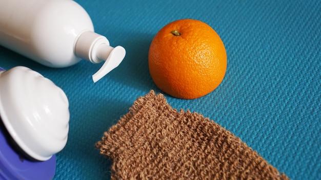 Balsam, pomarańcza, gąbka pod prysznic i masażer antycellulitowy na niebieskim tle. koncepcja zdrowej i pięknej skóry.