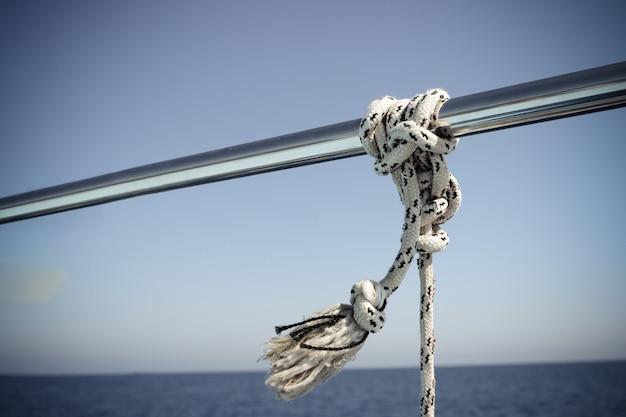 Balustrada do łodzi ze stali nierdzewnej z węzłem morskim. węzeł błotnika morskiego wokół łodzi lee. close-up żeglarskie liny węzeł na żaglówce.