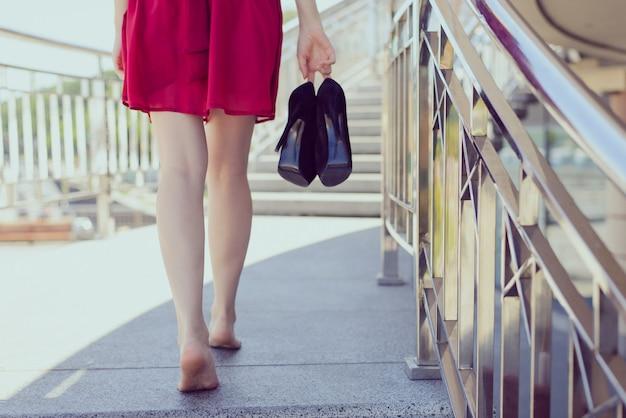 Balustrady balkon taras kierunek przyszły problem z blistrami dyskomfort koncepcja chodnika. tył za plecami z bliska zdjęcie szczęśliwej beztroskiej beztroskiej kobiety niosącej pompy w ręku, niewyraźne tło