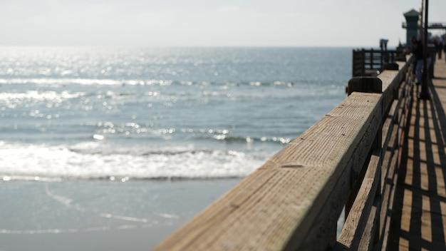 Balustrady starego drewnianego molo, ludzie chodzą na promenadzie nabrzeża, atmosfera plaży nad oceanem, kalifornijskie wybrzeże usa. rozmyty pejzaż morski, fale na pacyfiku. letnie wakacje w los angeles.